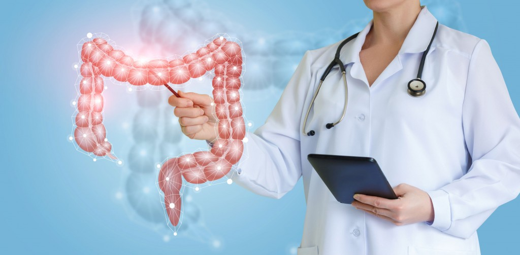 Doctor shows colon on virtual screen over blue background.
